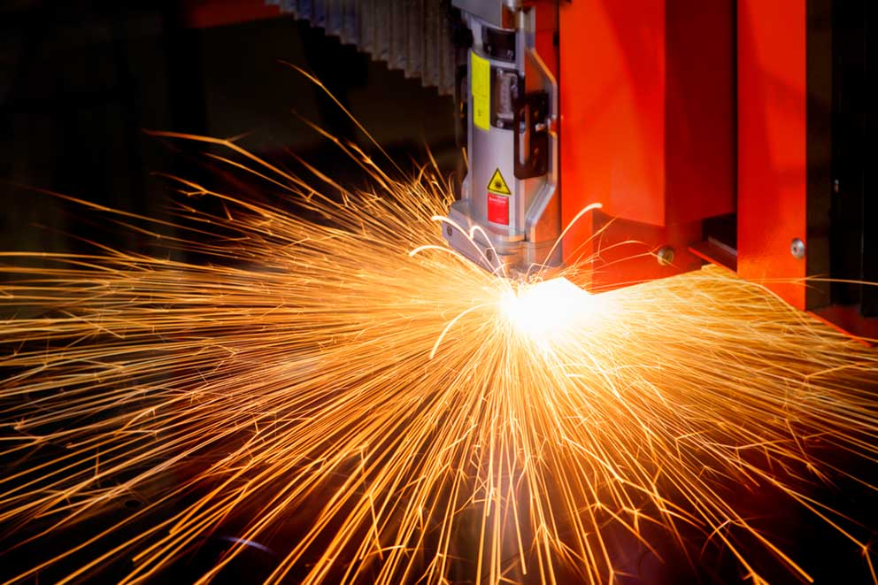 Laser cutter cutting metal orange sparks light trails manufacturing industrial photography image
