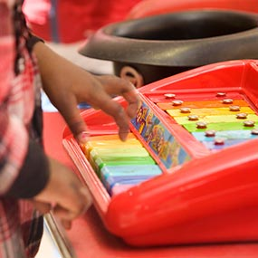 Child playing colourful keyboard at nursery school